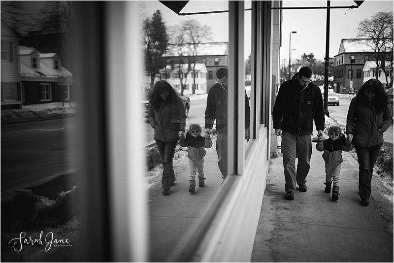 Window reflection of family walking down sidewalk Sarah Jane photography Maine