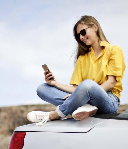 blond girl on the trunk of a car useing the phone
