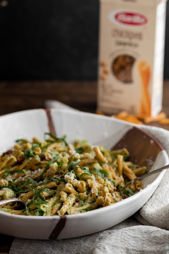Side angle photograph of a chickpea pasta tossed in a broccoli pesto, served in a large white dish.