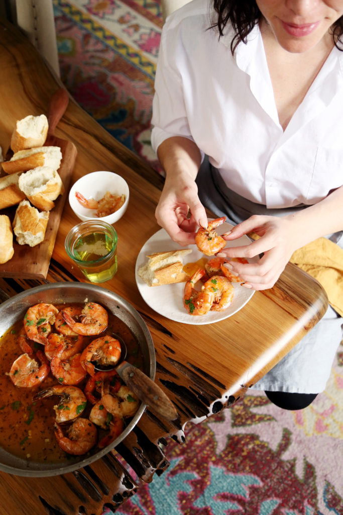 Peeling New Orleans style bbq shrimp on a plate with crusty bread.