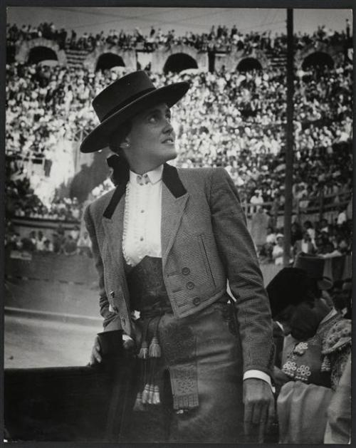 """Matadora Conchita Cintrón, Arles, France, 1949 (Brassaï)One of the world's premier rejoneadores and the most-respected matadora in bullfighting history, Cintrón retired at the age of 27 after a legendary bullfight in Jaén, Spain.In the final moments of this performance, she rode over to the presidente's box and asked permission to break the Spanish law forbidding a woman from dismounting her horse and fighting the bull on foot. Her request was denied.But instead of peacefully exiting the arena, Cintrón dismounted anyway and rushed the unsuspecting young male understudy assigned to kill her bull. She grabbed his sword and muleta (the small red cape used in the final act of a bullfight) and shocked the crowd by caping the bull and preparing it for the kill. She lined up the animal with the sword and then, in dramatic fashion, let the blade drop to the sand; the bull charged, whereupon Cintrón softly simulated the kill by touching the bull on the shoulders as it thundered by.The audience erupted into cheers, throwing hats and red carnations at her feet. Cintrón walked calmly away from the bull and was arrested at ringside. With the audience on the verge of rioting in protest of her arrest, Cintrón was pardoned and released. It was one of the most dramatic moments in bullfighting history.As Orson Welles, who wrote the introduction to Cintrón's autobiography, Memoirs of a Bullfighter, concluded, the matadora's career """"ended in a single burst of glorious criminality. You can't keep a lady waiting forever, and there came an afternoon when she decided that she'd waited long enough."""""""