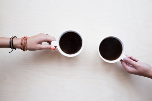 Photo: Two hands of two people, each pulling a mug of black coffee over.