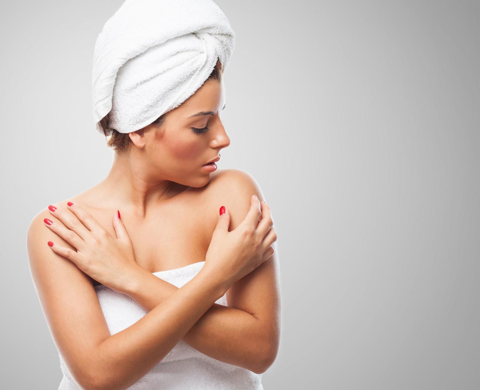 lupus mulher vestida com uma toalha no corpo e no cabelo olhando para o proprio ombro lupus