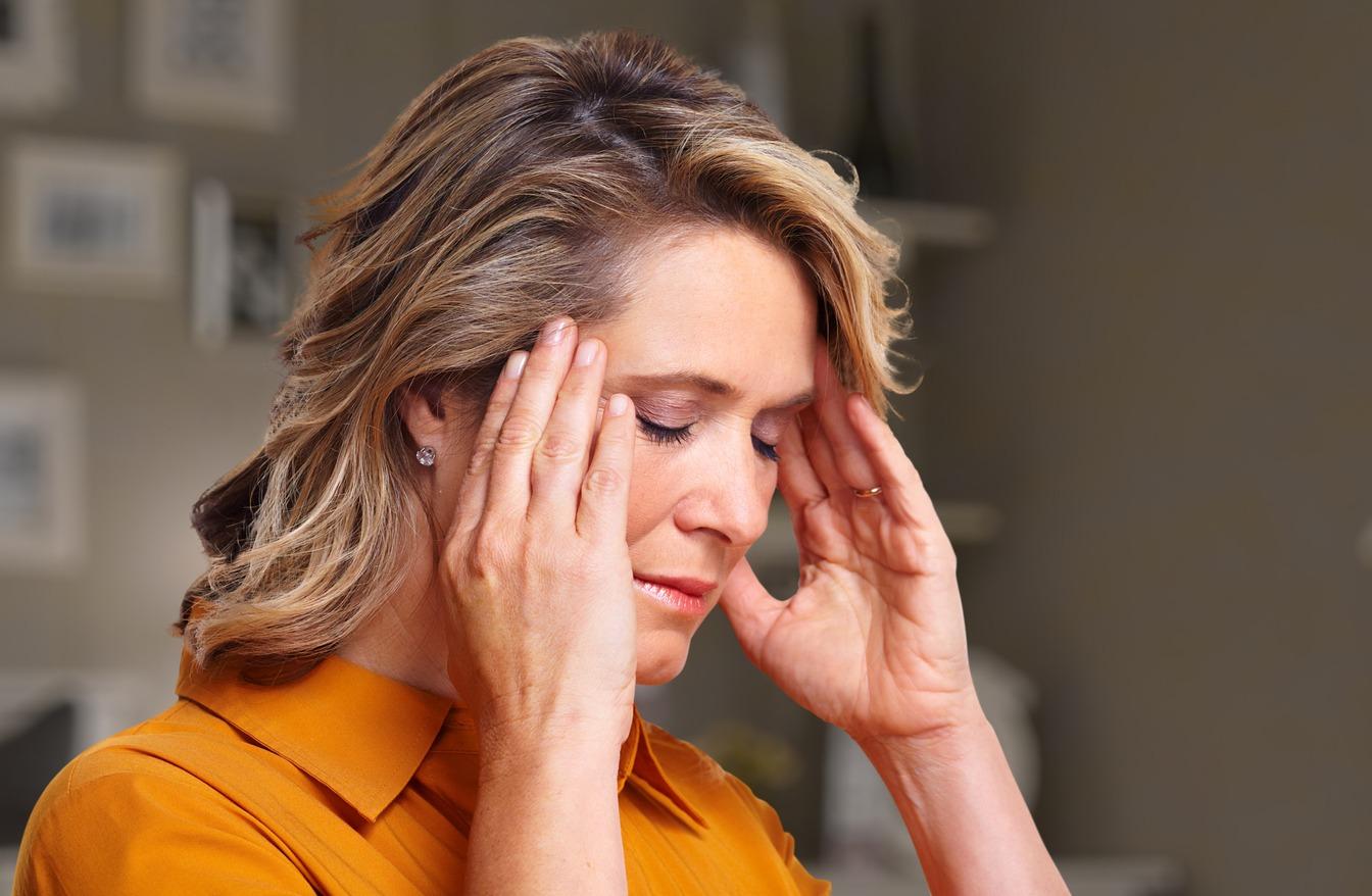 mulher com as maos na cabeca com aspecto de dor