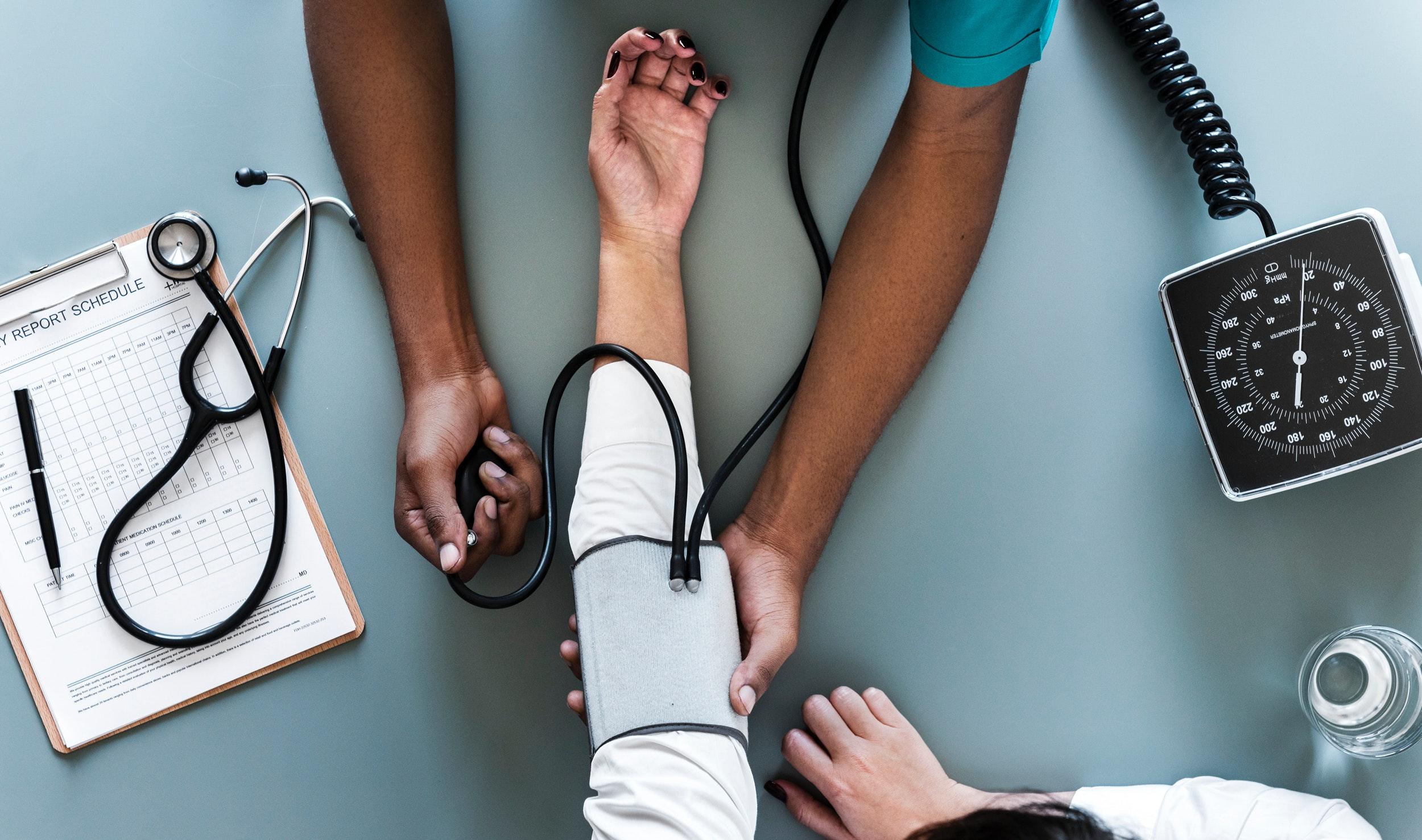 medico examinando a pressao arterial do paciente