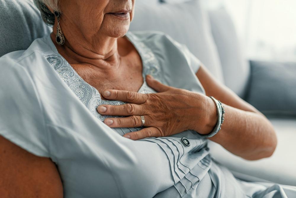 mulher da terceira idade com a mao no peito do lado direito