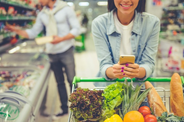 Couple in supermarket using mobile retail chatbot to find ingredients