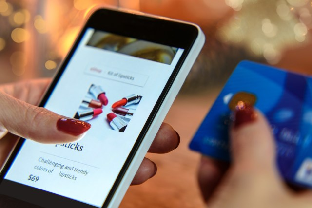 Woman on mobile phone using retail chatbot to shop for lipstick