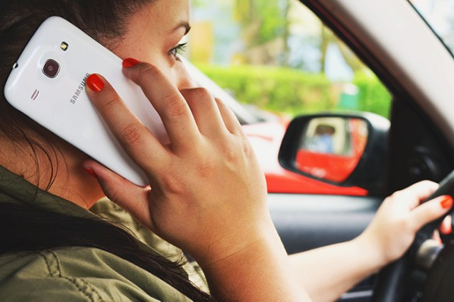 woman talking on smartphone while driving car