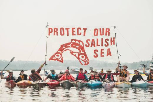 """Photo of kayaktivists holding """"Protect Our Salish Sea"""" banner"""