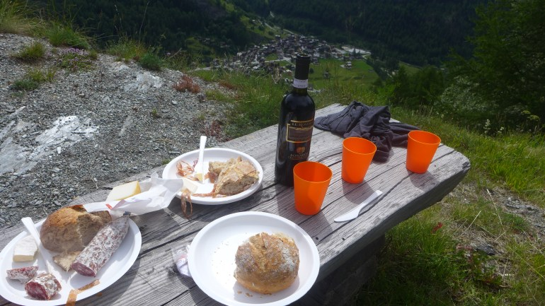 A lunch of bread, cheese and cured meats, overlooking a village