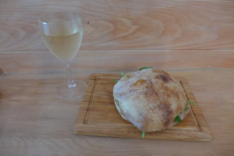 Tuna and anchovy sandwich, paired with a glass of white wine