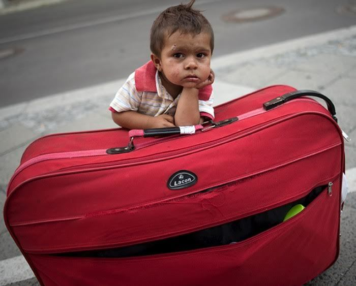 A migrant boy waits at his parents' suitcase as they leave the Berlin State Office for Health and Social Affairs with other newly arrived refugees who waited all day to apply for asylum in Berlin. REUTERS/Stefanie Loos