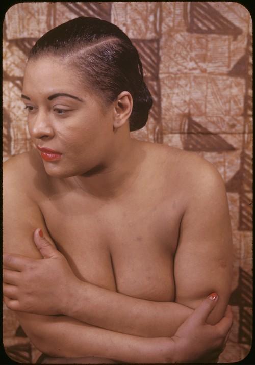 """Billie Holiday, con l'aiuto e il supporto di Artie Shaw, fu tra le prime cantanti nere ad esibirsi assieme a musicisti bianchi, superando le barriere razziali.[9] La Holiday nei locali dove cantava doveva comunque utilizzare l'ingresso riservato ai neri, e rimanere chiusa in camerino fino all'entrata in scena. Una volta sul palcoscenico, si trasformava in Lady Day: portava sempre una gardenia bianca tra i capelli, che divenne il suo segno distintivo.  Nel 1939, sfidando le discriminazioni razziali che colpivano i neri, cantò una canzone coraggiosa, Strange Fruit (Grammy Hall of Fame Award 1978): il frutto era il corpo di un nero ucciso dai bianchi ed appeso a un albero. La canzone divise il pubblico; la Holiday poté eseguirla solo se la direzione del club lo consentiva previamente.  Billie Holiday nel 1949 All'inizio degli anni quaranta la sua vita subì due forti scosse: un matrimonio breve e tormentato e la morte della madre. Prostrata, cominciò ad assumere stupefacenti, dalla marijuana fino all'eroina.   Venne in Italia una sola volta, nel 1958 a Milano, dal 3 al 9 novembre ma in un teatro di avanspettacolo. Il pubblico, non abituato al jazz, non gradì lo spettacolo e la Holiday non poté nemmeno cantare tutti i brani in scaletta: dopo il quinto pezzo venne fatta tornare in camerino[10]. Il 9 novembre, ultimo giorno di permanenza a Milano della cantante, fu organizzato da appassionati e intenditori di jazz uno spettacolo """"riparatore"""" al Gerolamo, in piazza Beccaria, grazie al fido Mal Waldron. Il pubblico le tributò una vera e propria ovazione. (da Wikipedia)"""