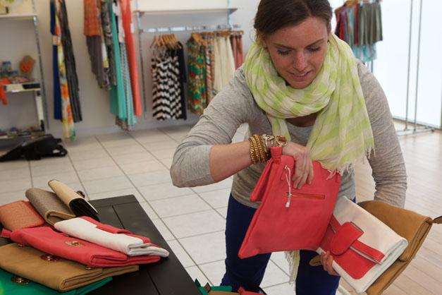 Annie Lang arranges handbags for a LUXE wearhouse pop-up event.  Photograph by Julie Linnekin