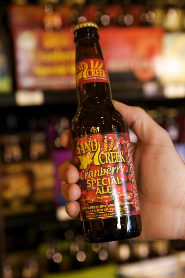 Scott Oliver, Heinen's Beer Lead, shows off Sand Creek Cranberry Ale - Photographed by Julie Linnekin