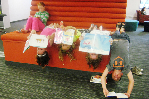 Youth Services Librarian Becky Fyolek caught these kids in a most unusual pose for reading...