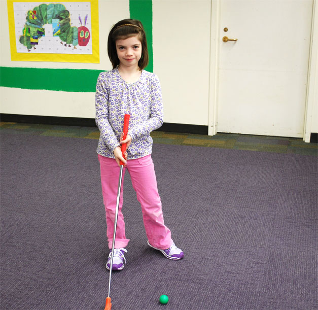 Little girl holding golf club.