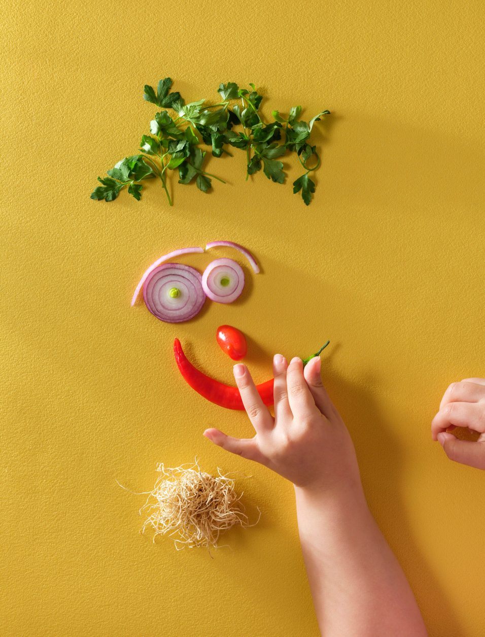Making smiley face with vegetables by little girl