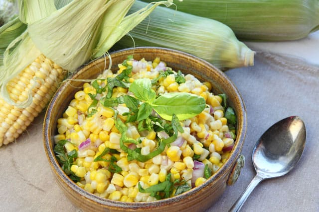 Fresh corn salad with red onion and basil makes a delicious BBQ side dish or potluck recipe
