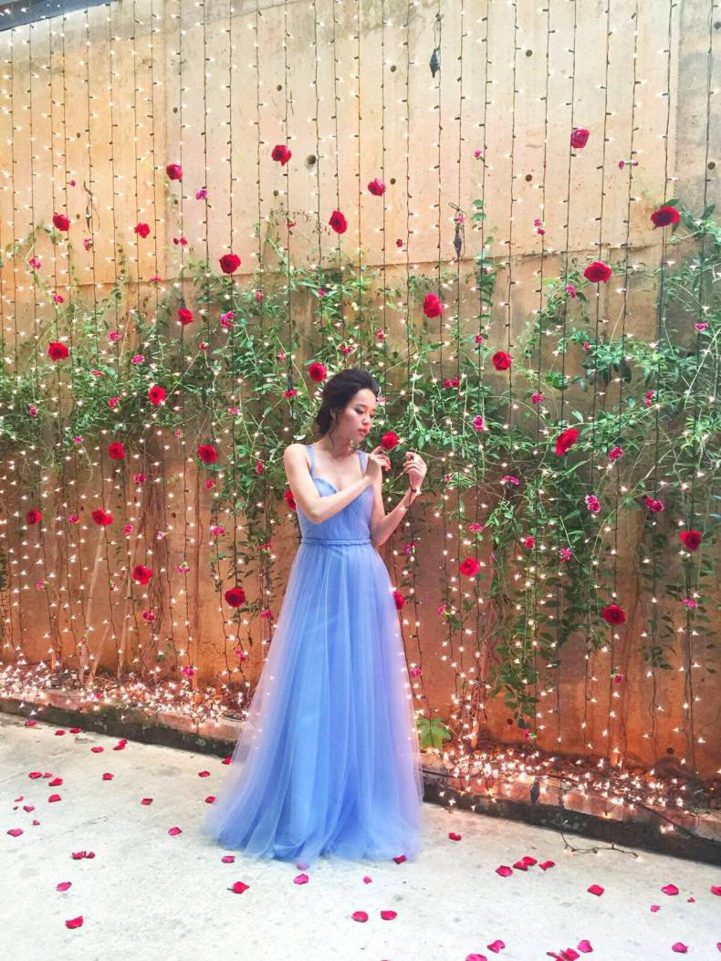 woman in ethereal periwinkle dress stands in front of a wall with green plants and vertical string lights with red flowers interspersed