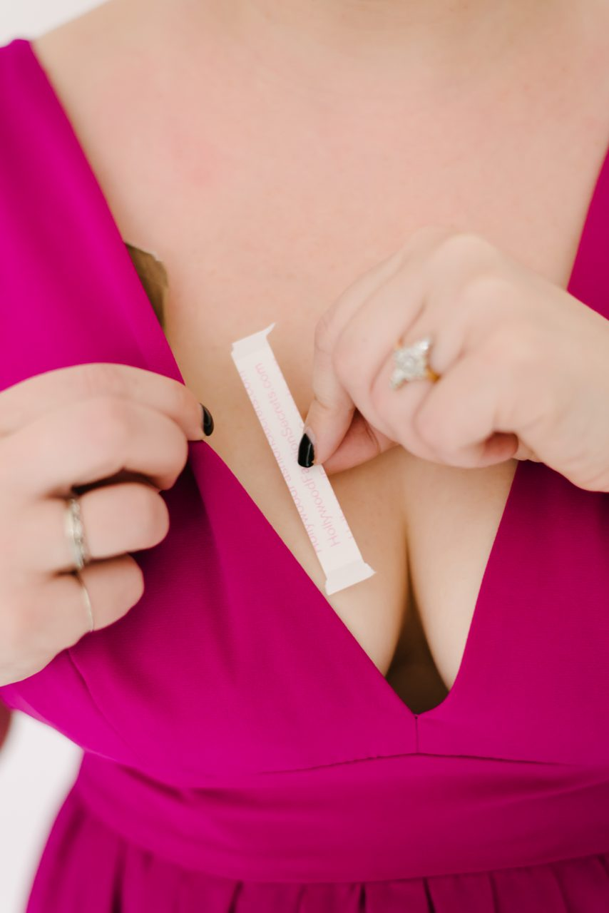 The Boob Tape Bra Trick That Really Works   A Practical Wedding closeup of fashion tape being put on neckline of pink dress