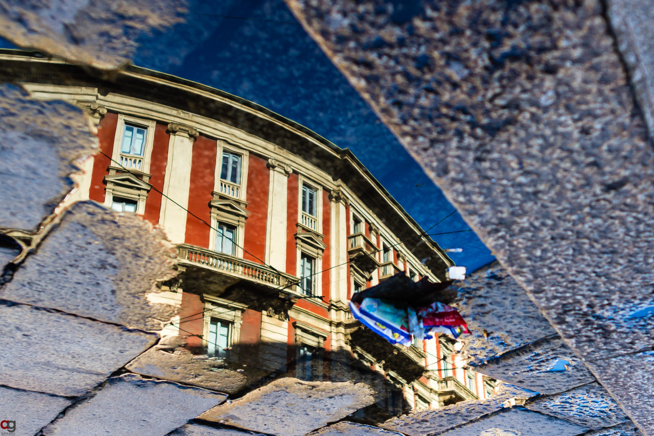 Urban Mirror - View of a historic building reflected in water on the ground