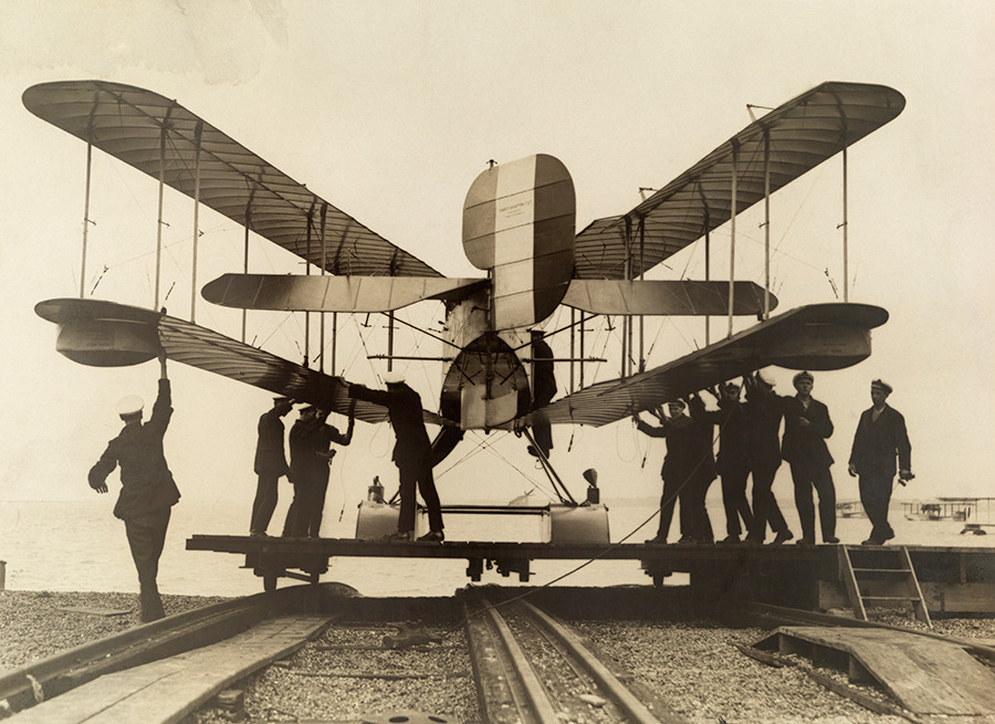 Men inspect a British airplane with folding wings, 1918.No Credit Given