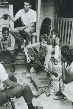 updownsmilefrown:</p> <p>Bob Dylan plays on the back of the SNCC office in Greenwood, Mississippi, 1963<br />