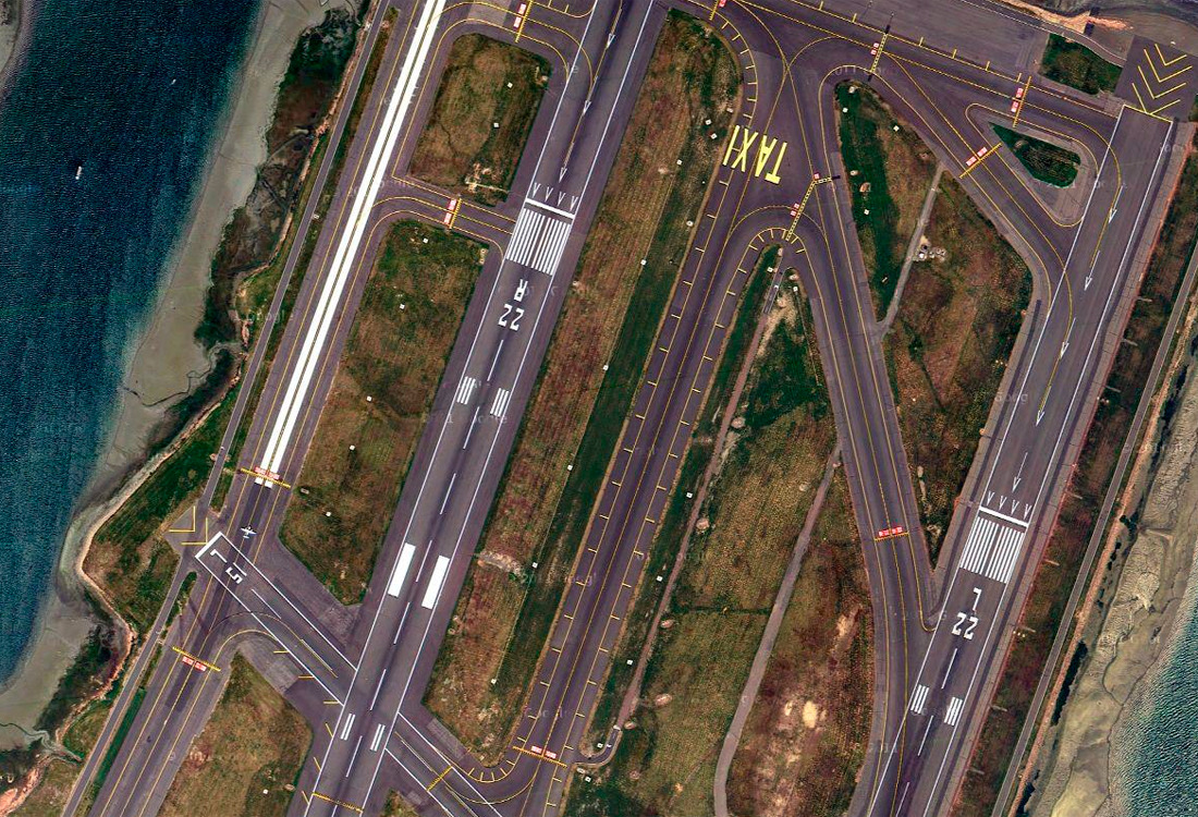 Parallel runways with strips of ocean on either side. One runway is marked 'TAXI'
