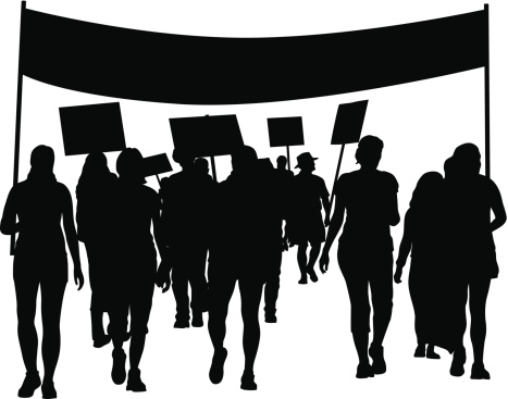 A silhouette of people carrying a banner and placards