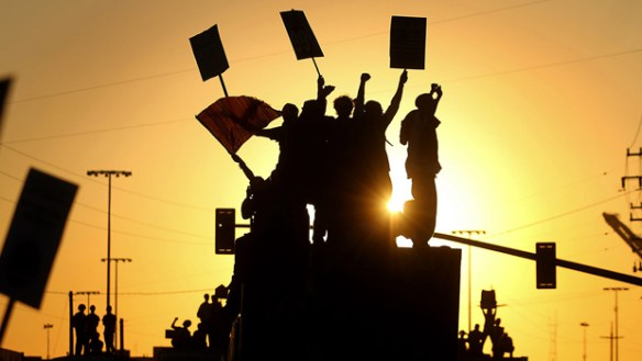 A silhouette of protesters at Occupy Oakland standing on a traffic median and raising placards and flags against an orange sunset