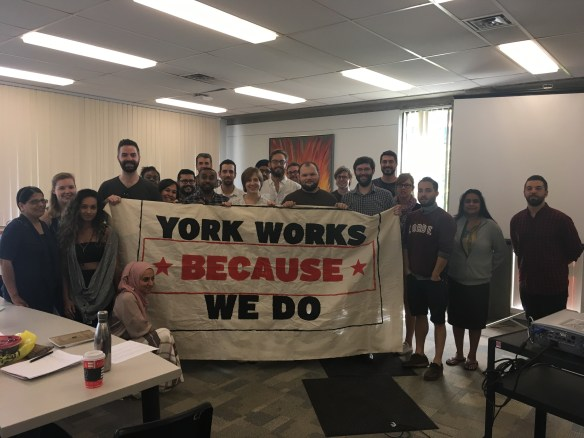 "Members of CUPE 3903 stand with a banner reading ""York Works Because We Do"" at the September 25 bargaining meeting."