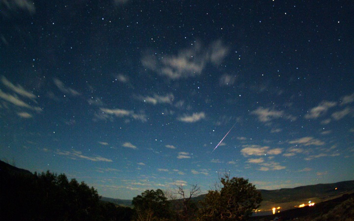 A perseid meteor streaks across a star-encrusted and cloud-scattered sky. Image Credit: Jimmy Westlake