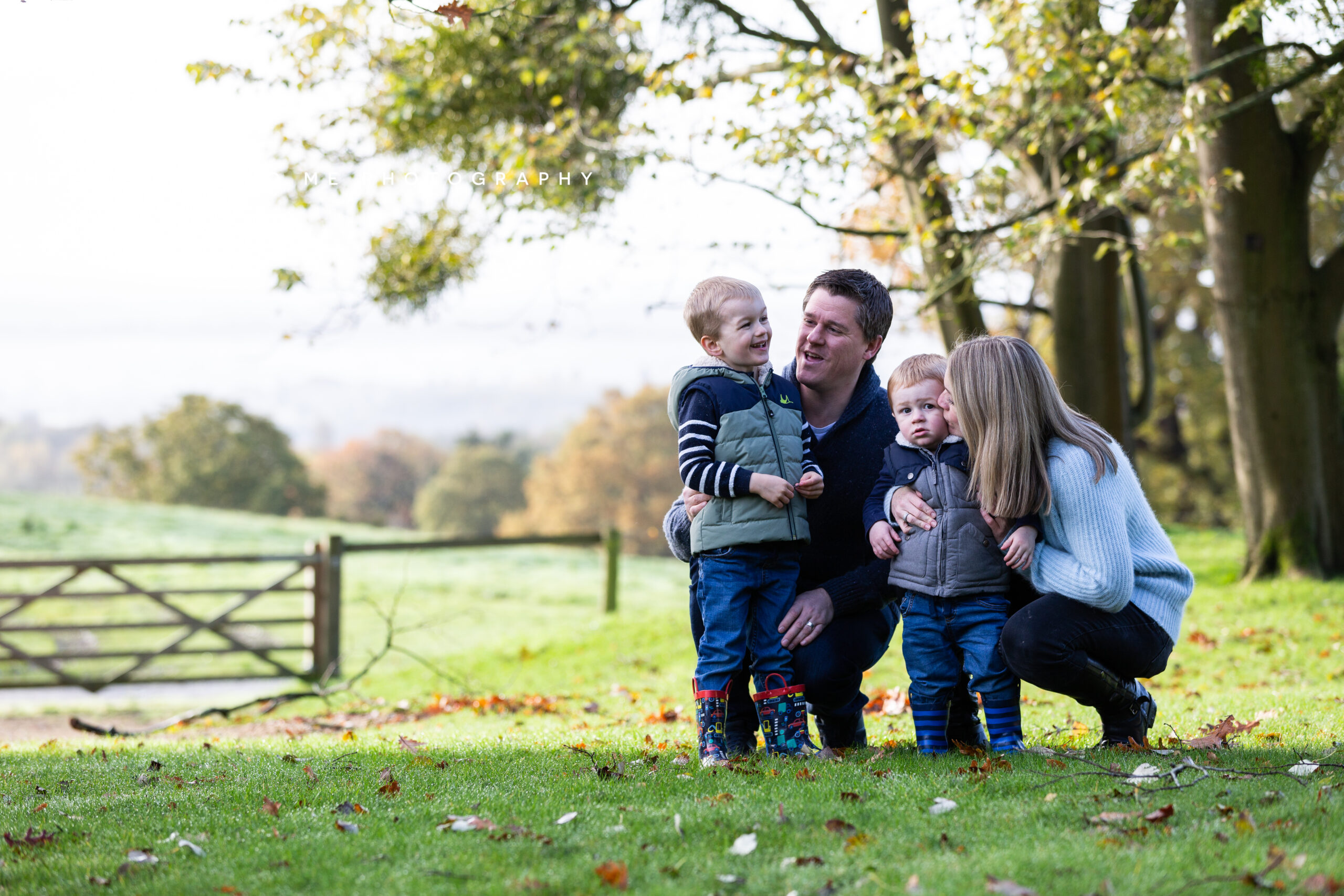family with two young boys playing on the grass at their autumn family photoshoot in Kent