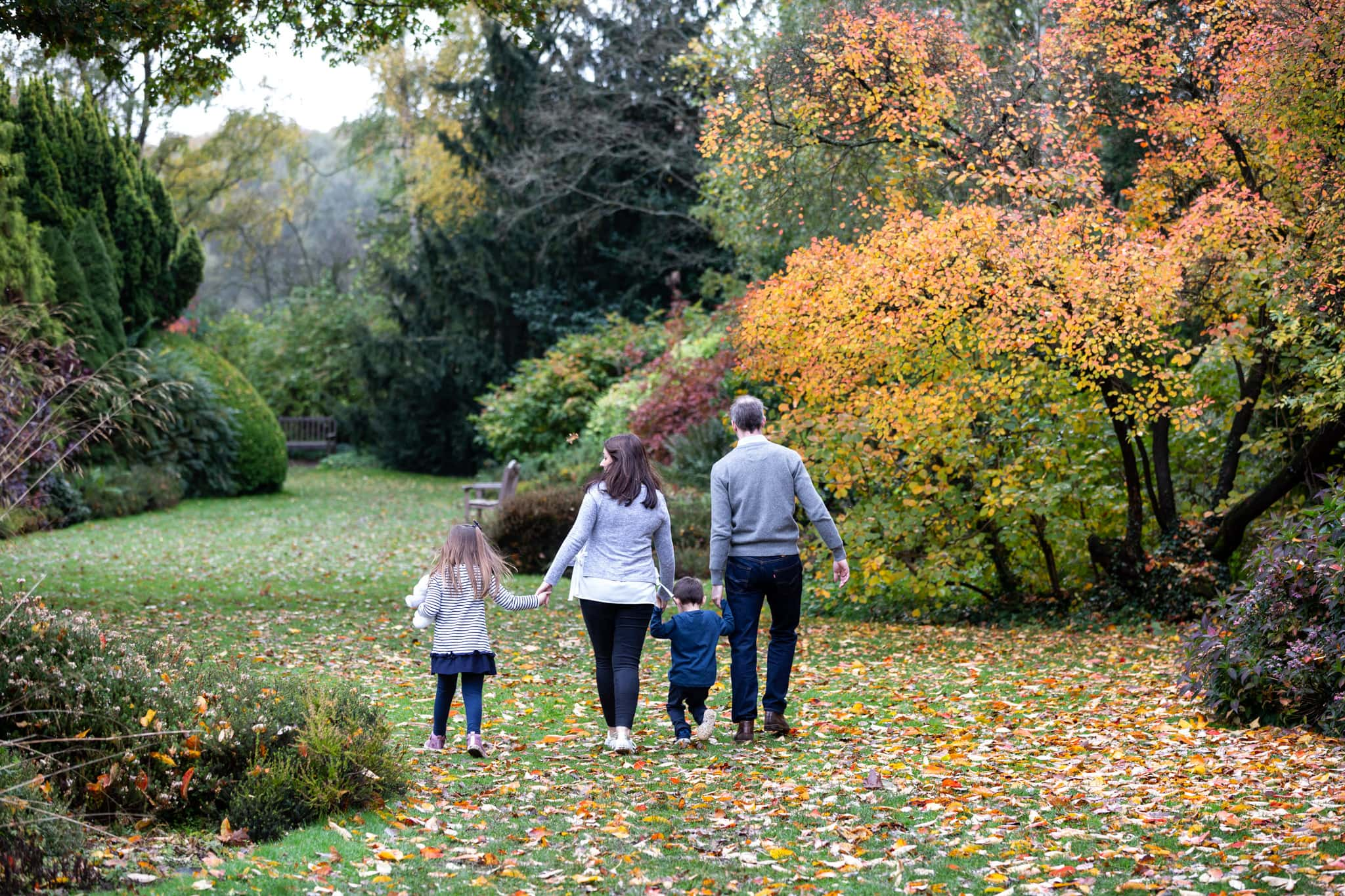 family of four walking away holding hand at their autumn photoshoot at Great Comp Gardens in Sevenoaks
