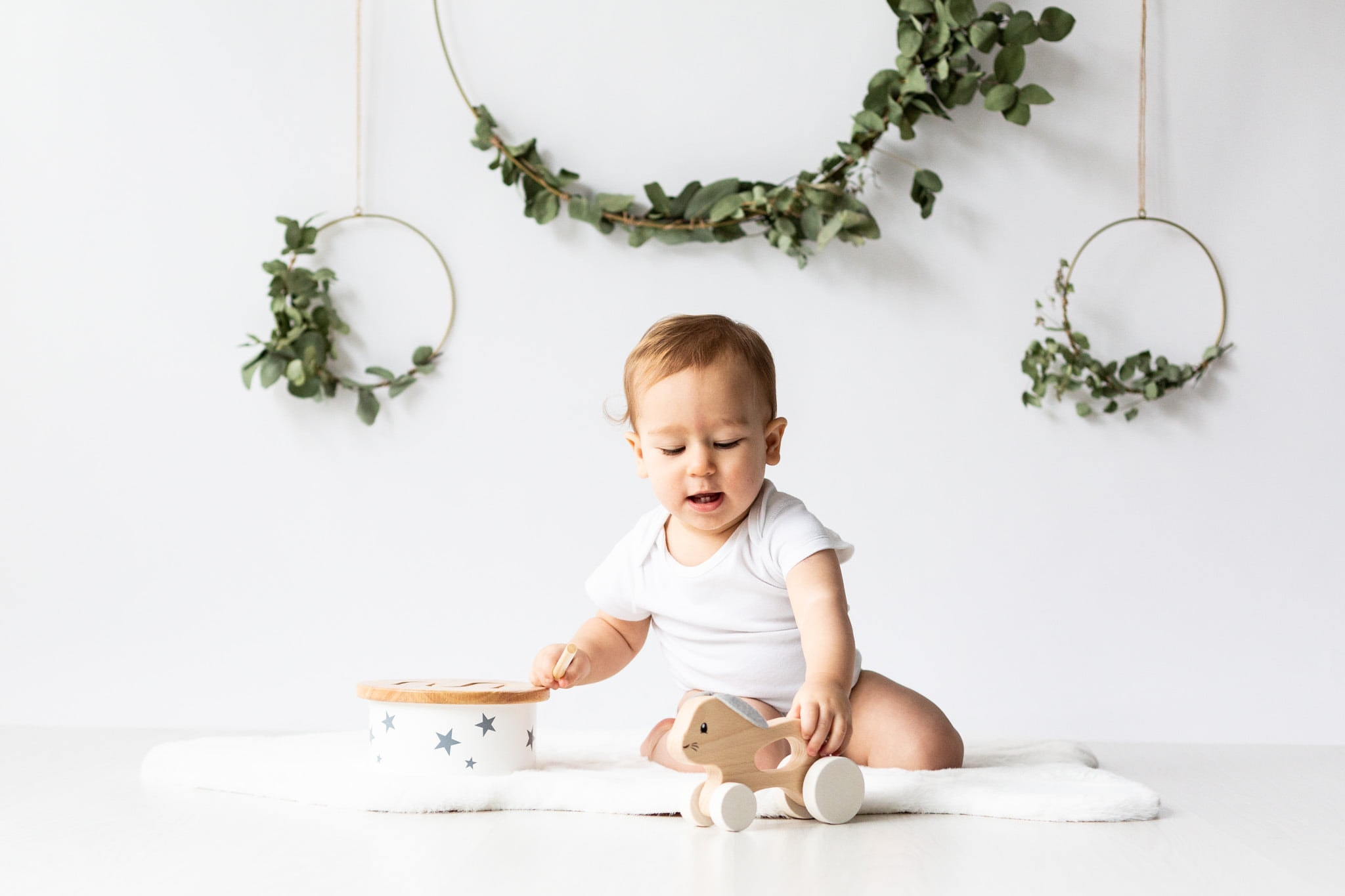 Little girl in white studio set up playing with wooden toys taken at the beginning of her cakesmash photoshoot in Bexley