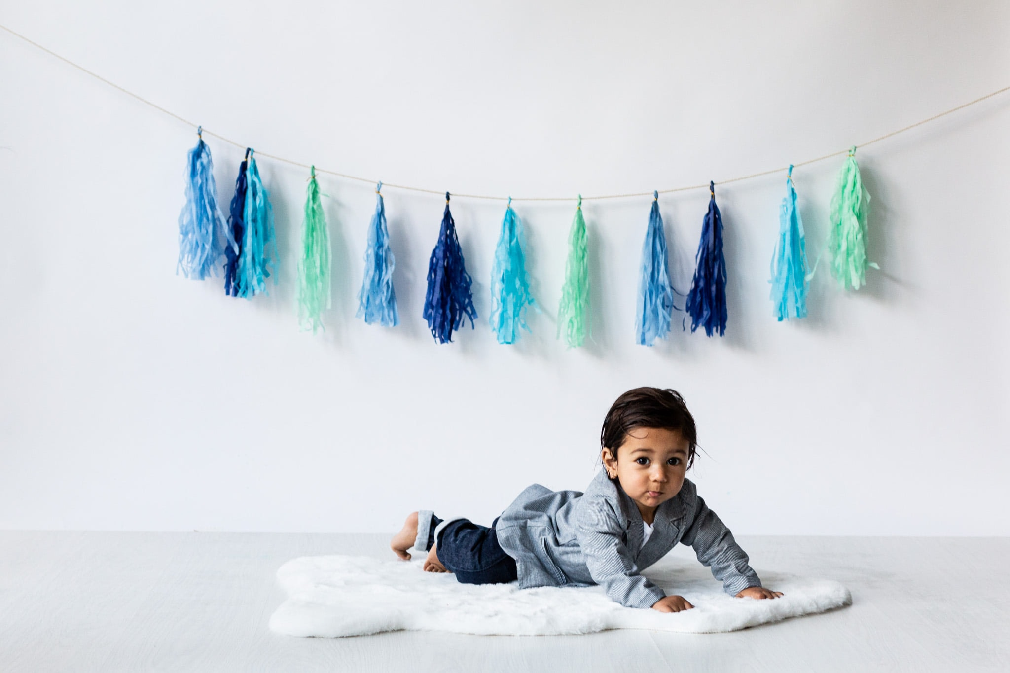 Little boy laying on fur rug at his Bexley cakesmash photoshoot