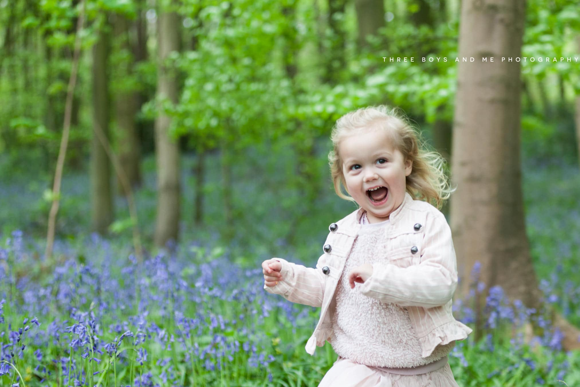 little girl wearing dusty pink laughing in the bluebells at her Bexley family photoshoot