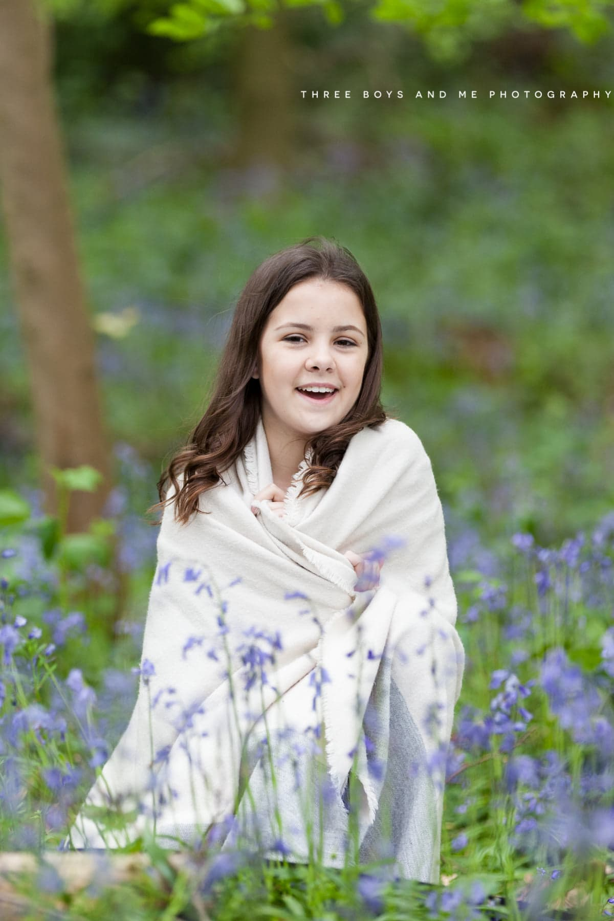 young girl wrapped in a shawl sat in the bluebells at her Bexley family bluebell shoot