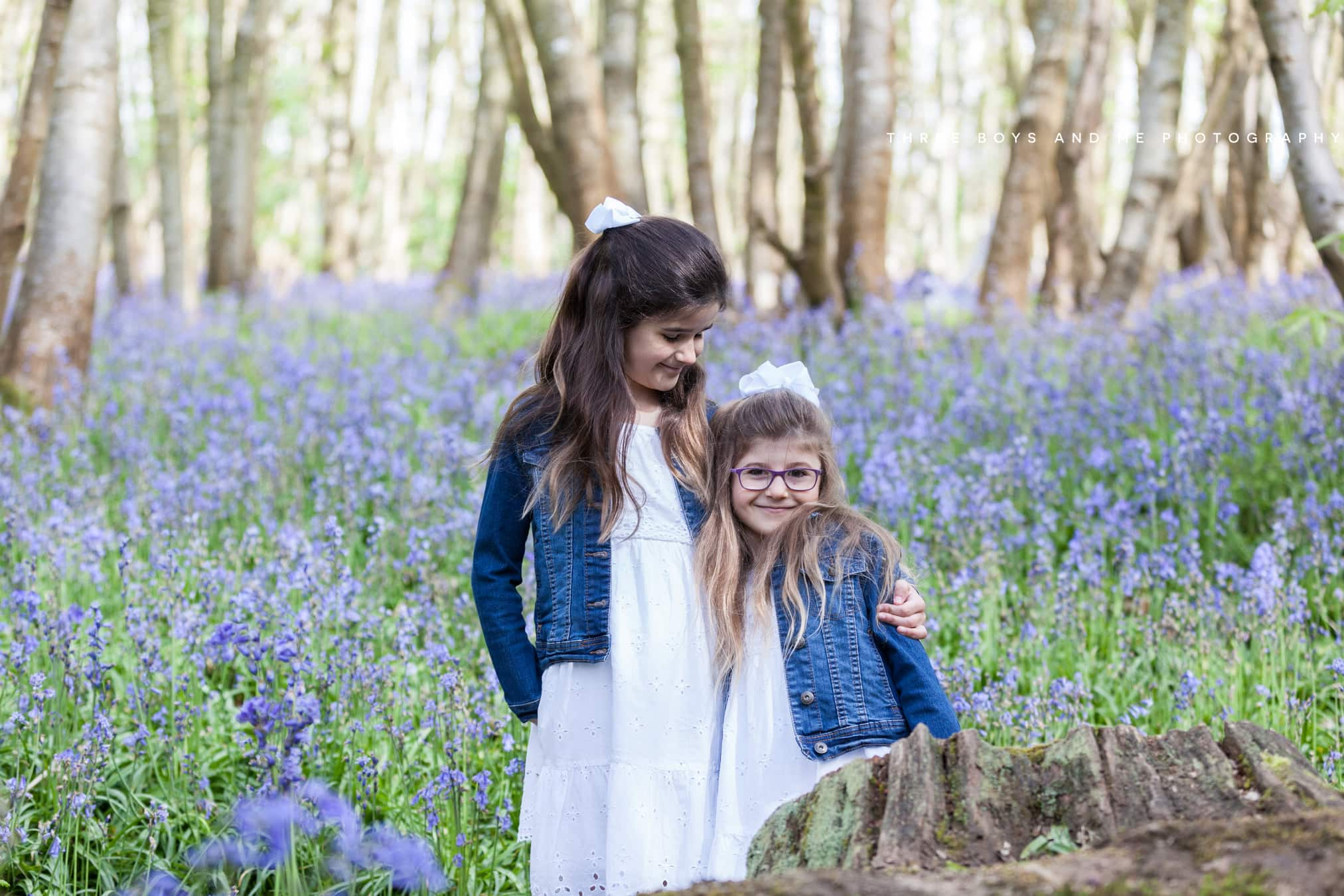 sisters dressed in white with denim jackets at their Sevenoaks family bluebell shoot