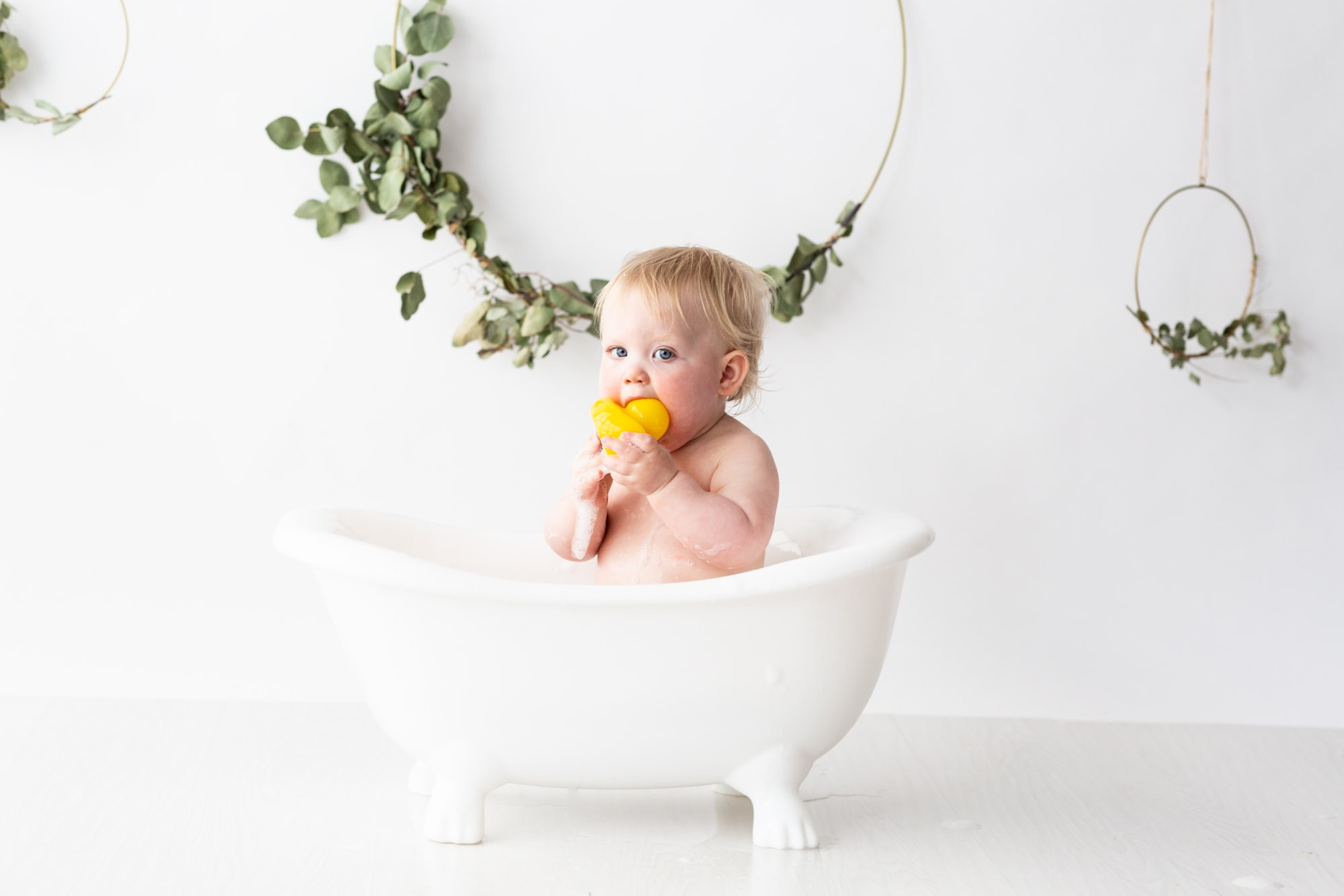 baby girl with yellow duck in white roll top plastic baby bath at her first birthday cake smash photoshoot in Bexley