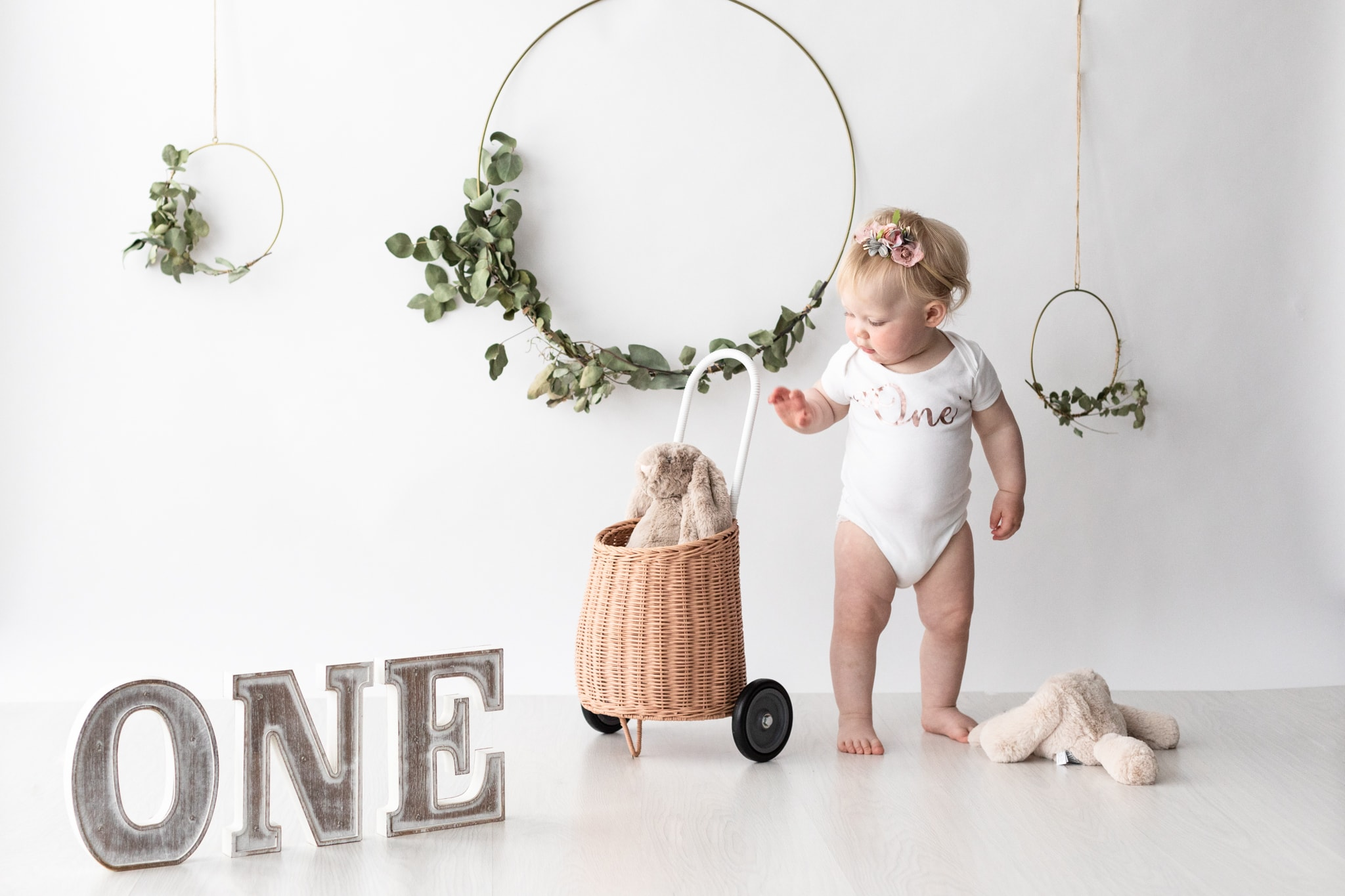 little girl with Olli and Ella shopping trolly in a neutral cake smash set up at her Kent Cake smash photoshoot