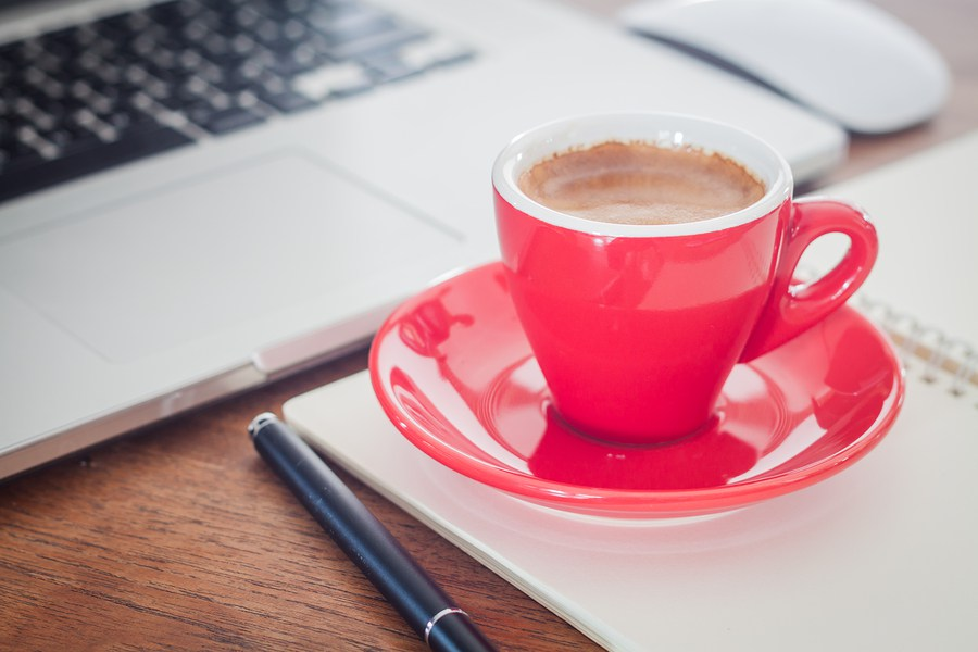 Red coffee cup sitting beside computer