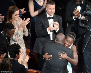 Lupita embraces 12 Years A Slave director Steve McQueen while producer Bra Pitt looks on