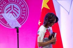 Peking 16- first lady Michelle Obama holds a book given to her as a gift from Peking University as she leaves a podium after her speech at Stanford Center in the Peking University