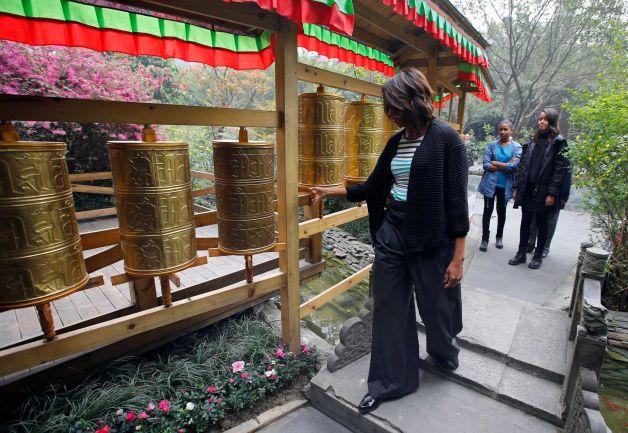 Tibetan- first lady Michelle Obama, left, touches Tibetan prayer wheels as her daughter Malia, right, and Sasha watch outside a Tibetan restaurant in Chengdu, Sichuan province, China Photo-Petar Kujundzic, AP