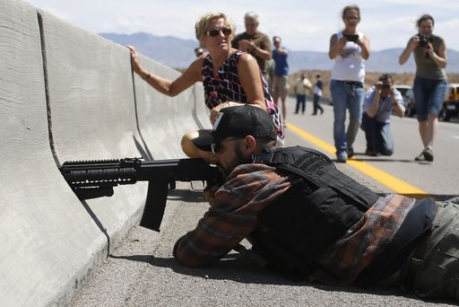Image: A protester aims his weapon from a bridge next to the Bureau of Land Management's base camp where seized cattle, that belonged to rancher Cliven Bundy, are being held at near Bunkerville