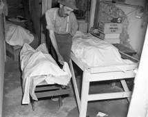 Coroner W.T. Brown on July 26, 1946, places a sheet over the body of one of the four African Americans lynched.
