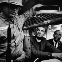 Freedom Riders on board interstate bus as they & 25 others are escorted by a Mississippi National Guardsman en route from Montgomery, AL to Jackson, MS.
